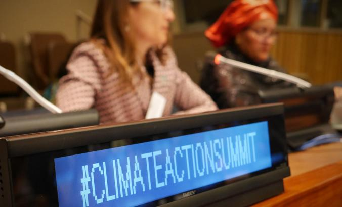 "Sign reads, ""#ClimateActionSummit."" Chilean Minister of Environment Carolina Schmidt and U.N. Deputy Secretary-General Amina J. Mohammed pictured in background."