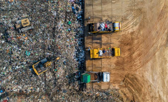 Aerial view of waste being disposed of in the waste disposal pits. Loaders is working on a mountain garbage.