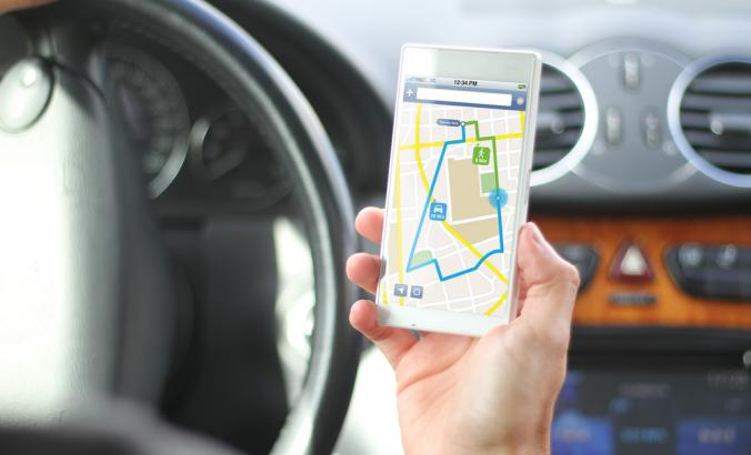 Driver holds phone that has mapped directions on screen