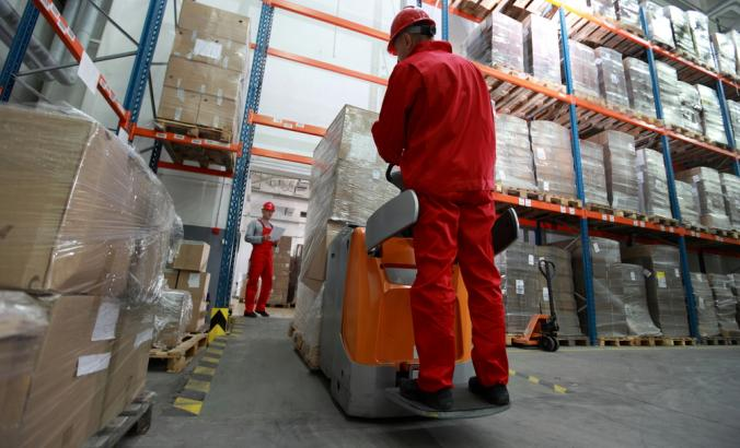 Two workers working in warehouse with forklift loader