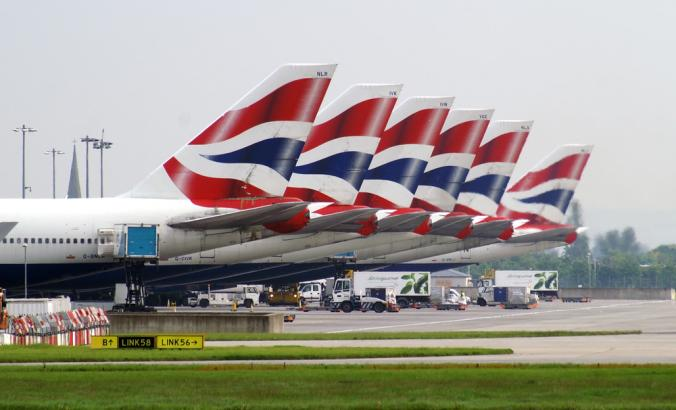 Fleet of Boeing 747 planes of British Airways standing on the apron of London Heathrow airport. The British flag, which is red, white and blue, is on the tail of the planes.