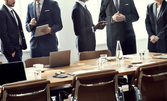 People wearing suit in a board meeting room. They're standing behind a table, which has glasses of water on top. You cannot see their faces in the image.