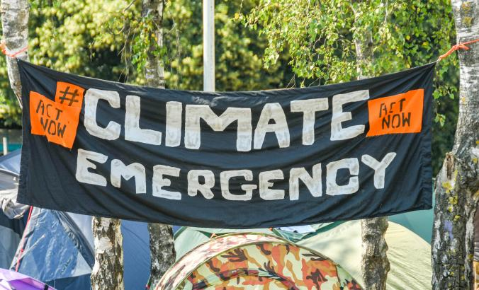 "A ""Climate Emergency"" banner hangs between trees in a makeshift campsite in Cardiff, Wales,"