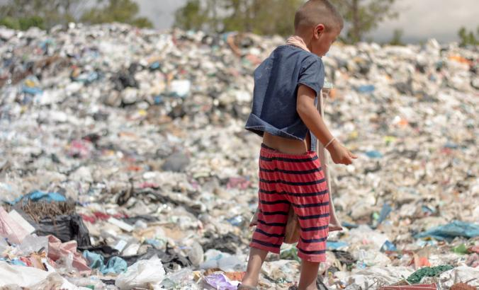A child picks up recyclable waste in a landfill