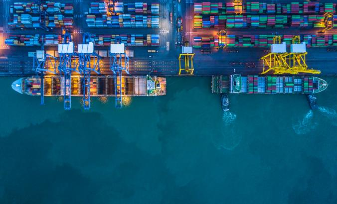 Container ship loading and unloading in deep sea port, aerial view