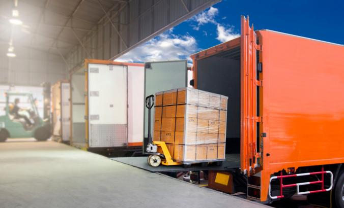 Forklift loading cargo into an orange truck.