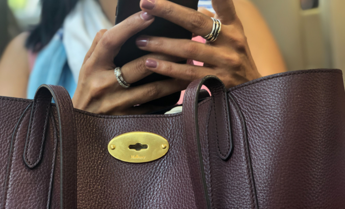 A person  rests their hand and mobile phone on their designer Mulberry bag, whilst messaging on their phone.