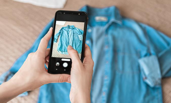 Person taking photo of denim shirt on smartphone