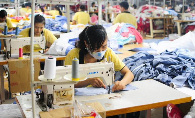 Garment factory employees working at sewing machines