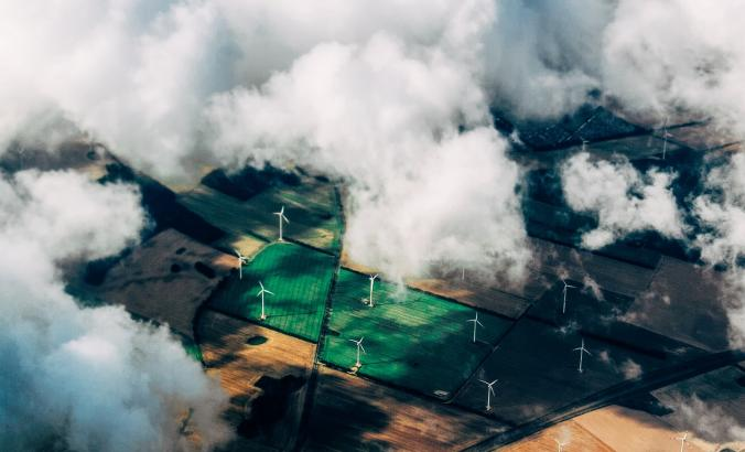 Aerial view of wind turbines from high in the sky. Clouds can be seen in the frame.