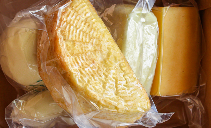 A pile of different types of packaged cheese